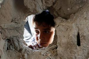 A boy looks through a hole on the wall made by the shelling at the Abu Hussein U.N. school in the Jebaliya refugee camp in the northern Gaza Strip on Wednesday, July 30, 2014. Some 3,300 Gazans seeking shelter from the fighting had been crowded into the U.N. school in Jebaliya refugee camp when it was hit by a series of Israeli artillery shells.  (AP Photo/Hatem Moussa)