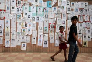 Two youths walk past a wall pasted with flyers showing some of the missing on Monday April 29, 2013 in Savar, near Dhaka, Bangladesh. Rescue workers in Bangladesh gave up hopes of finding any more survivors in the remains of a building that collapsed five days ago, and began using heavy machinery on Monday to dislodge the rubble and look for bodies -- mostly of workers in garment factories there. At least 381 people were killed when the illegally constructed, 8-story Rana Plaza collapsed in a heap on Wednesday morning along with thousands of workers in the five garment factories in the building.(AP Photo/Wong Maye-E)