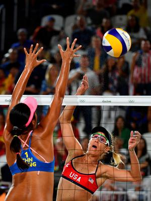 China's Wang Fan (L) tries to block the ball during the women's beach volleyball qualifying match between the USA and China at the Beach Volley Arena in Rio de Janeiro late on August 8, 2016, for the Rio 2016 Olympic Games. / AFP PHOTO / Leon NEALLEON NEAL/AFP/Getty Images