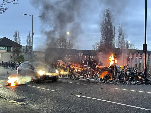 A car drives past the wreckage of a Translink Metrobus on fire on the Shankill Road (Liam McBurney/PA)