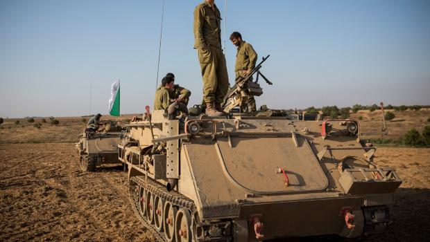 "SDEROT, ISRAEL - JULY 15:  An Israeli soldier stands on top of an armored personnel carrier near the Israeli-Gaza border on July 15, 2014 near Sderot, Israel.  As operation 'Protective Edge"" enters it's eighth day of airstrikes by the Israel Defense Forces (IDF) across the Gaza Strip, Egypt has this morning tabled a ceasefire agreement proposing a halting of fighting starting at 9am. Once violence has ceased, the proposal calls for Israel to open a border crossing into Gaza to allow the movement of goods and people. Israel has accepted the Egyptian proposal for a truce, however it is thought Hamas has rejected the deal.  (Photo by Andrew Burton/Getty Images)"
