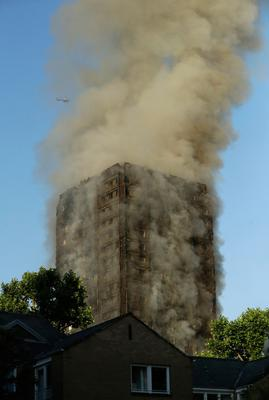 Smoke rises from a building on fire in London, Wednesday, June 14, 2017. Metropolitan Police in London say they're continuing to evacuate people from a massive apartment fire in west London. The fire has been burning for more than three hours and stretches from the second to the 27th floor of the building.(AP Photo/Matt Dunham)