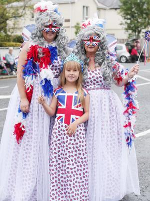 Press Eye - Belfast -  Northern Ireland - 13th July  2015  Belfast's Orange Order annual 12th of July demonstration makes its way through the City Centre to the field at Malone House beside Shaws Bridge.  Left to right.  Norma Moore, Jodie Moore(8) and Thomasena Hunt wait for the parade on Balmoral Avenue.   Picture by Jonathan Porter/Press Eye