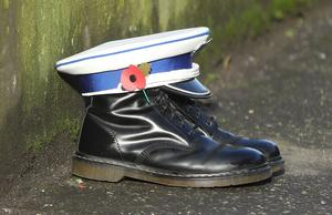 A loyalist flute band cap and boots are left in tribute at Cluan Place (Niall Carson/PA)