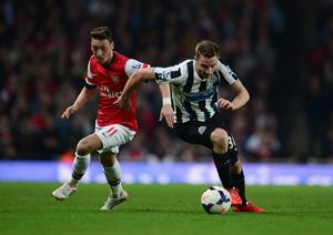 LONDON, ENGLAND - APRIL 28:  Paul Dummett of Newcastle United chases the ball with Mesut Oezil of Arsenal during the Barclays Premier League match between Arsenal and Newcastle United at Emirates Stadium on April 28, 2014 in London, England.  (Photo by Jamie McDonald/Getty Images)