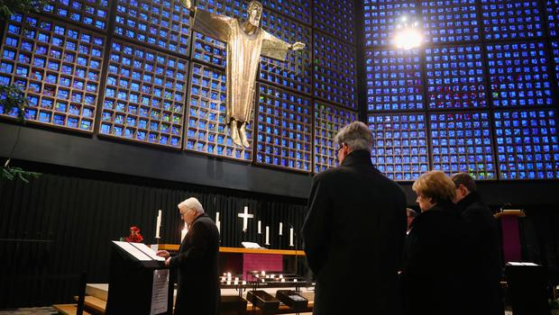 BERLIN, GERMANY - DECEMBER 20:  German Chancellor Angela Merkel (2nd from R) looks on as Foreign Minister Frank-Walter Steinmeier signs a book of condolences at the Kaiser Wilhelm Memorial Church the day after a truck drove into an adjacent, crowded Christmas market on December 20, 2016 in Berlin, Germany. So far 12 people are confirmed dead and 45 injured. Authorities have confirmed they believe the incident was an attack and have arrested a Pakistani man who they believe was the driver of the truck and who had fled immediately after the attack. Among the dead are a Polish man who was found on the passenger seat of the truck. Police are investigating the possibility that the truck, which belongs to a Polish trucking company, was stolen yesterday morning.  (Photo by Sean Gallup/Getty Images)