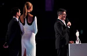 LONDON, ENGLAND - FEBRUARY 25:  Simon Cowell accepts the British Video of the Year Award for One Direction from Jimmy Carr and Karlie Kloss at the BRIT Awards 2015 at The O2 Arena on February 25, 2015 in London, England.  (Photo by Gareth Cattermole/Getty Images)