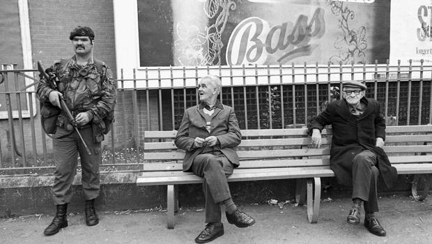 Two old men on a bench and a Marine Commando playing with his safety-catch of his rifle, at Sugar Island in the centre of Newry Co. Down, on a Twelfth of July around 1985. Newry was over 90% Catholic and the occasion would be tense with very few people were on the streets but police and soldiers.  I spotted this scene and mentally framed the picture. It was illegal by definition to photograph 'the Security Forces' so I asked the soldier 'can I take a picture' and I think he nodded, so I fired one frame (shooting 35mm black-and-white film very sparingly), then I waited, shot another one, waited again and then the man in the middle looked up and that's my picture. Someone told me he's a Marine Commando and he's playing with the safety-catch of the rifle. From The SeaÃÅn Hillen Collection of photographs recently acquired by the National Library of Ireland Photographic Archive
