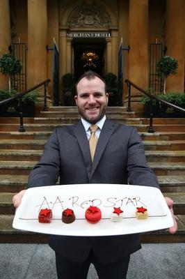General Manager of The Merchant Hotel Gavin Carroll celebrates after the AA upgraded hotel's rating from five black stars to five red stars at the prestigious AA Hospitality Awards