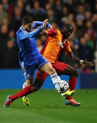 LONDON, ENGLAND - MARCH 18:  Eden Hazard of Chelsea battles with Emmanuel Eboue of Galatasaray during the UEFA Champions League Round of 16 second leg match between Chelsea and Galatasaray AS at Stamford Bridge on March 18, 2014 in London, England.  (Photo by Clive Rose/Getty Images)
