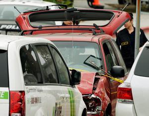 SANTA MONICA, CA - JUNE 07:  Law enforcement personal invstigate the shooting scene where an SUV crashed throught the wall of a parking lot and hit several cars across the street from the Santa Monica College weher a multiple shootings happened on campus June 7, 2013 in Santa Monica, California. According to reports, seven people are dead including the shooter and three people were injured.  (Photo by Kevork Djansezian/Getty Images)