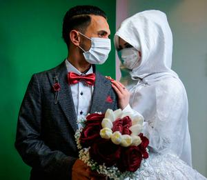 Mohamed abu Daga and his bride Israa, wearing face masks, are allowed to have their wedding ceremony in Palestine