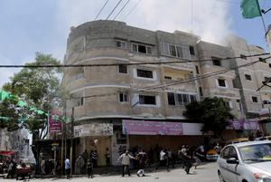 Palestinian worshippers run to take cover when an Israeli strike hit the roof of a building across from Al Qassam mosque, where they were offering Friday prayer in Nusseirat refugee camp in the central Gaza Strip on Friday, Aug. 1, 2014. (AP Photo/Adel Hana)