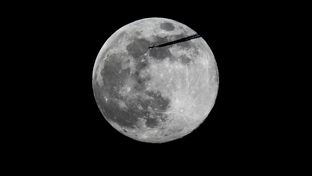 A plane passes the pink supermoon as it rises over Dublin (Brian Lawless/PA)