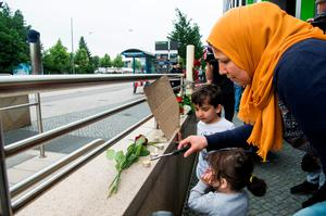 MUNICH, GERMANY - JULY 23: A woman and her children lay flowers and candles outside the OEZ shopping center the day after a shooting spree left nine victims dead on July 23, 2016 in Munich, Germany. According to police an 18-year-old German man of Iranian descent shot nine people dead and wounded at least 16 before he shot himself in a nearby park. For hours during the spree and the following manhunt the city lay paralyzed as police ordered people to stay off the streets. Original reports of up to three attackers seem to have been unfounded. The shooter's motive is so far unclear. (Photo by Joerg Koch/Getty Images)