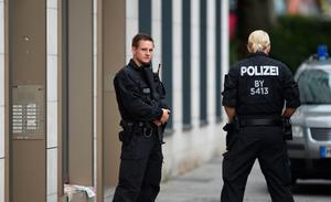 Policemen stand in front of an apartment building in Munich's Dachauer Strasse street on July 23, 2016, one day after the attack at the shopping centre in Munich. Police were probing the motives of the lone teenage German-Iranian gunman who went on a deadly rampage at a busy Munich shopping centre, the third bloody attack on civilians in Europe in just over a week. Nine people were killed and another 16 wounded as the black-clad gunman brought terror to Germany's third largest city on Friday evening, July 22, 2016, before committing suicide. / AFP PHOTO / dpa / Tobias Hase / Germany OUTTOBIAS HASE/AFP/Getty Images