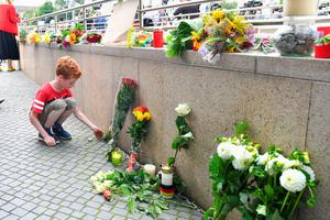 A little boy puts down flowers near a mall where a shooting took place leaving nine people dead the day before on Saturday, July 23, 2016 in Munich, Germany. (AP Photo/Kerstin Joensson)