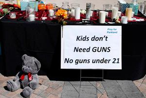 Candles, flowers and stuffed animals serve as a  memorial for the victims of the Marjory Stoneman Douglas High School shooting in a park in Parkland, Florida on February 16, 2018  A former student, Nikolas Cruz, opened fire at the Florida high school leaving 17 people dead and 15 injured. / AFP PHOTO / RHONA WISERHONA WISE/AFP/Getty Images