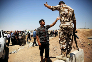 An Iraqi man argues with a Kurdish soldier as Iraqis who have fled recent fighting in the cities of Mosul and Tal Afar try to enter a temporary displacement camp but are blocked by Kurdish soldiers on July 2, 2014 in Khazair, Iraq. (Photo by Spencer Platt/Getty Images)
