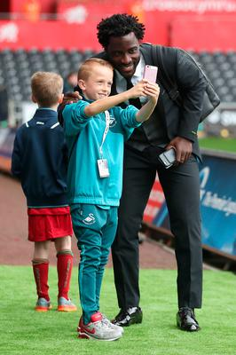 The beautiful game - football fans from around the world -  Swansea City's Wilfried Bony takes a picture with a young fan prior to the Premier League match at the Liberty Stadium, Swansea.