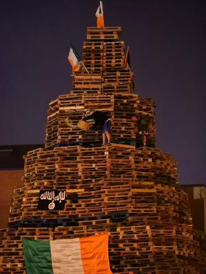 A man lights an 11th night Bonfire in the Sandy Row area of Belfast.  PRESS ASSOCIATION Photo. Picture date: Thursday July 12, 2018. Hundreds of bonfires were set to be lit at midnight as part of a loyalist tradition to mark the anniversary of the Protestant King William's victory over the Catholic King James at the Battle of the Boyne in 1690. See PA story ULSTER Bonfires. Photo credit should read: Niall Carson/PA Wire