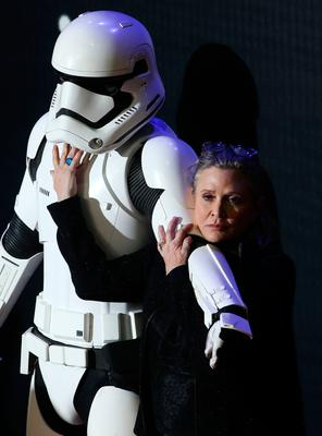 """(FILES) This file photo taken on December 16, 2015 shows US actress Carrie Fisher attending the opening of the European Premiere of """"Star Wars: The Force Awakens"""" in central London.  Hollywood star Carrie Fisher -- best known for her portrayal of Princess Leia in the """"Star Wars"""" saga -- died December 27, 2016, days after suffering a massive heart attack on a transatlantic flight, according to a family statement given to People magazine. """"It is with a very deep sadness that Billie Lourd confirms that her beloved mother Carrie Fisher passed away at 8:55 this morning,"""" family spokesman Simon Halls said in a statement on behalf of Fisher's daughter.  / AFP PHOTO / JUSTIN TALLISJUSTIN TALLIS/AFP/Getty Images"""