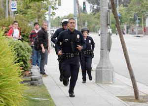 SANTA MONICA, CA - JUNE 07:  Students look on as Los Angeles Police Department Officers deploy around the Santa Monica College near the library after multiple shootings were reported on June 7, 2013 in Santa Monica, California. According to reports, at least one person has died, four people hospitalized, and a suspect was taken into custody. (Photo by Kevork Djansezian/Getty Images)