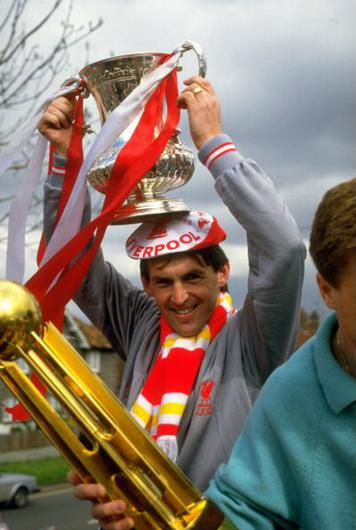 Kenny Dalglish of Liverpool holding the trophy aloft during their homecoming after the FA Cup final against Everton