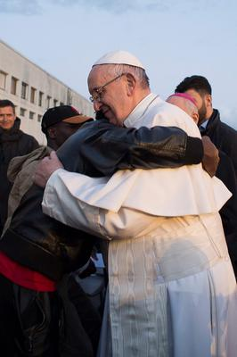 Pope Francis hugs a migrant during his visit at the Castelnuovo di Porto refugees center, some 30km (18, 6 miles) from Rome, Thursday, March 24, 2016. The pontiff washed and kissed the feet of Muslim, Orthodox, Hindu and Catholic refugees Thursday, declaring them children of the same God, in a gesture of welcome and brotherhood at a time when anti-Muslim and anti-immigrant sentiment has spiked following the Brussels attacks. (L'Osservatore Romano/Pool Photo via AP)