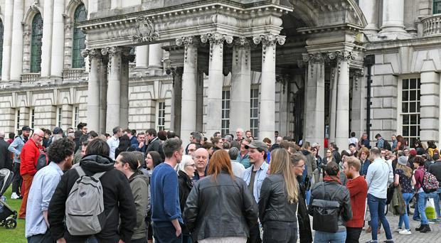 Members of the public gather to pay tribute at Belfast City Hall