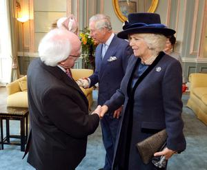 The President of Ireland Michael D Higgins shakes hands with the Duchess of Cornwall, as she and the Prince of Wales welcome him to the UK for a five day state visit, at the Irish Embassy in central London