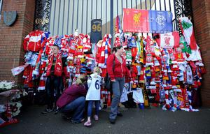 A fan ties a scarf to the Shankly Gates at Anfield, before the Hillsborough 25th Anniversary Memorial Service