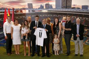 Welsh international soccer player Gareth Bale, his relatives, and Real Madrid President Florentino Perez pose during his official presentation at the Santiago Bernabeu stadium  in Madrid, Spain, Monday, Sept. 2, 2013 after signing for Real Madrid. The Spanish club announced Sunday that Bale has signed a six-year contract, and a person familiar with the deal said the fee was a world-record euro100 million ($132 million).  (AP Photo/Daniel Ochoa de Olza)
