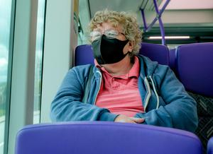 A passenger wearing a mask on the Glider in Belfast yesterday