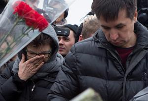 People react as they lay flowers at the place where Boris Nemtsov was gunned down (AP Photo/Denis Tyrin)