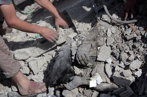 Palestinians try to dig a body out of the rubble of a destroyed house hit by an Israeli strike during a 12-hour cease-fire in Gaza City's Shijaiyah neighborhood, Saturday, July 26, 2014.(AP Photo/Khalil Hamra)