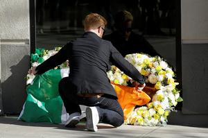 Neil Sands of the Irish Network Bay Area places a flag of Ireland over wreaths at the Library Gardens apartment complex in Berkeley, Calif., Tuesday, June 16, 2015 (AP Photo/Jeff Chiu)