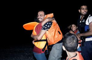 "Migrants hug one another after getting out of an inflatable boat on a beach on the Greek island of Kos, after crossing a part of the Aegean Sea between Turkey and Greece, on August 12, 2015. The number of migrants and refugees arriving on Greece's shores has exploded this year, but the Mediterranean country provides virtually no reception facilities and leaves them wallowing in ""totally shameful"" conditions, a UN official said on August 7.  The UN refugee agency's division for Europe said 124,000 refugees and migrants have landed in Greece since the beginning of the year.  AFP PHOTO / ANGELOS TZORTZINISANGELOS TZORTZINIS/AFP/Getty Images"