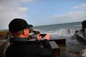 A man uses a smartphone camera at the 40 Foot swimming area on the Irish Sea coast at Glenageary, County Dublin, on October 16, 2017 as Ireland braces for the passing of the storm Ophelia.  / AFP PHOTO / Ben STANSALLBEN STANSALL/AFP/Getty Images
