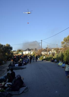 Migrants gather outside the camp as a helicopter tackles the fire (Panagiotis Balaskas/AP)