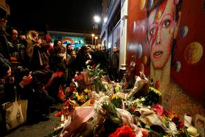 LONDON, ENGLAND - JANUARY 11: A man leaves flowers beneath a mural of David Bowie in Brixton on January 11, 2016 in London, England. British music and fashion icon David Bowie died earlier today at the age of 69 after a battle with cancer. (Photo by Carl Court/Getty Images)