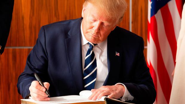 SHANNON, IRELAND - JUNE 05: US President Donald Trump signs the visitors book following his arrival at Shannon Airport on June 5, 2019 in Shannon, Ireland. After visiting the UK for the D-Day 75th anniversary, US President Donald Trump will visit Ireland to meet with Taoiseach Leo Varadkar before travelling to the Trump International Golf Links resort in Doonbeg. (Photo by Pool/Getty Images)