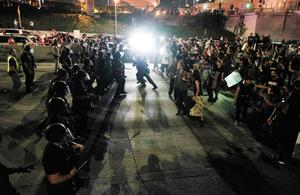 """Protesters (R) confront police as they shut down the 101 Freeway, a major thoroughfare in the city, following a rally to protest a day after President-elect Donald Trump's election victory in Los Angeles, California, late on November 9, 2016. Protesters burned a giant orange-haired head of Donald Trump in effigy, lit fires ins the streets and blocked traffic lanes late on November 9 as rage over the billionaire's election victory spilled onto the streets of US cities. From New York to Los Angeles, thousands of people in around 10 cities rallied against the president-elect a day after his stunning win, some carrying signs declaiming """"Not our President"""" and """"Love trumps hate."""" / AFP PHOTO / RINGO CHIURINGO CHIU/AFP/Getty Images"""