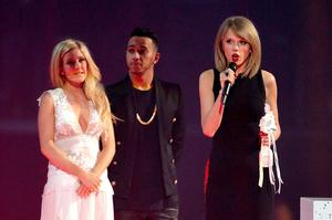 Taylor Swift receives her award for the International Female Solo Artist on stage from Ellie Goulding (left) and Lewis Hamilton (centre) during the 2015 Brit Awards at the O2 Arena, London