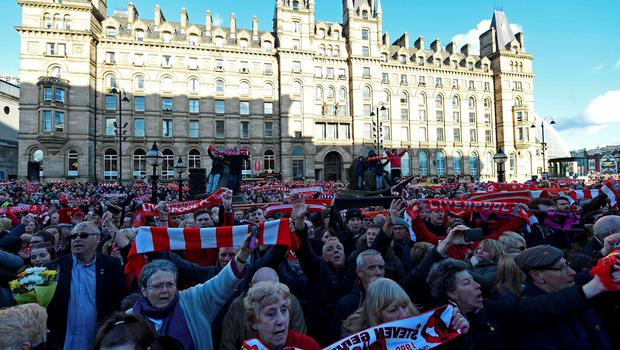 """People hold Liverpool football scarves in the air as they sing """"You'll Never Walk Alone"""" outside St George's Hall in Liverpool, north west England on April 27, 2016, during an event held in remembrance of the 96 Liverpool fans who died in the 1989 Hillsborough football stadium disaster. AFP/Getty Images"""