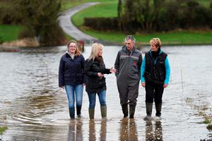 Minister Michelle O'Neill with local farmers, Gary McManus and Bridget McCaffrey (right) and Kathleen McCaffrey (left), as she views the impact of flooding on homes, roads and farmland at Innishroosk outside Lisnaskea. PA