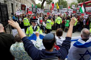 Police stand between pro-Israeli (foreground) and pro-Palestinian demonstrators outside the gates of Downing Street in London on September 9, 2015. Over 100 pro-Israeli demonstrators and hundreds of pro-Palestinian activists rallied in front of Downing Street in London ahead of a planned visit of Israeli Prime Minister Benjamin Netanyahu. Netanyahu visits Britain this week for talks with his counterpart David Cameron as the right-wing Israeli leader faces diplomatic pressure over West Bank settlements and stalled peace efforts. AFP PHOTO / JUSTIN TALLISJUSTIN TALLIS/AFP/Getty Images