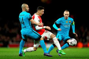 LONDON, ENGLAND - FEBRUARY 23: Javier Mascherano and Andres Iniesta of Barcelona tackle Mesut Ozil of Arsenal during the UEFA Champions League round of 16 first leg match between Arsenal and Barcelona at Emirates Stadium on February 23, 2016 in London, United Kingdom.  (Photo by Paul Gilham/Getty Images)