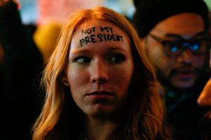A woman looks on as she takes part in a protest against President-elect Donald Trump in front of Trump Tower in New York on November 10, 2016. / AFP PHOTO / KENA BETANCURKENA BETANCUR/AFP/Getty Images