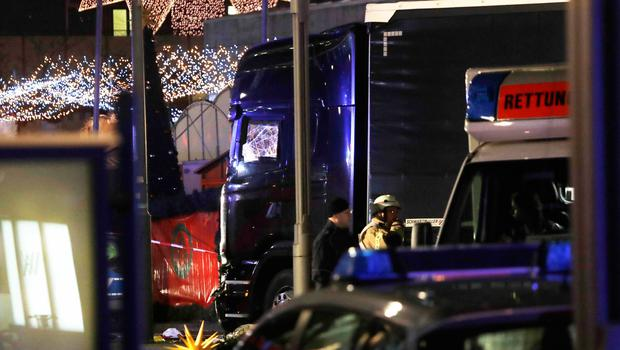 Police stand beside a damaged truck which ran into crowded Christmas market in Berliin Berlin, Germany, Monday, Dec. 19, 2016. (AP Photo/Michael Sohn)